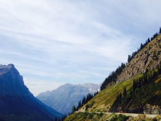A red bus cruises along the Going-to-the-Sun Road.